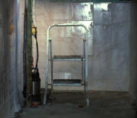 Gemauerte Regenwasser-Zisterne - Innenansicht mit Leiter und Tauchdruckpumpe.