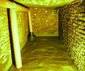 Gemauerte Regenwasser-Zisterne - Innenansicht unverputz mit Lehmboden und beruhigtem Einlauf.