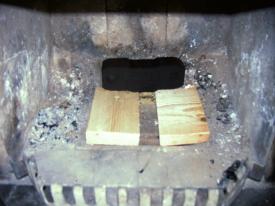 Kaminofen-Beschickung Bild 1: Das teilweise abgedeckte Kaminofen-Rost beschleunigt den Luftstrom zum Anheizen. Das optionale Brikett sorgt für eine gleichmäßigere hohe Wärmeleistung.